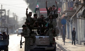 "Turkey-backed Syrian rebel fighters in the border town of Tal Abyad. The US-Turkey agreement calls for a 120-hour ceasefire in a ""safe zone""."