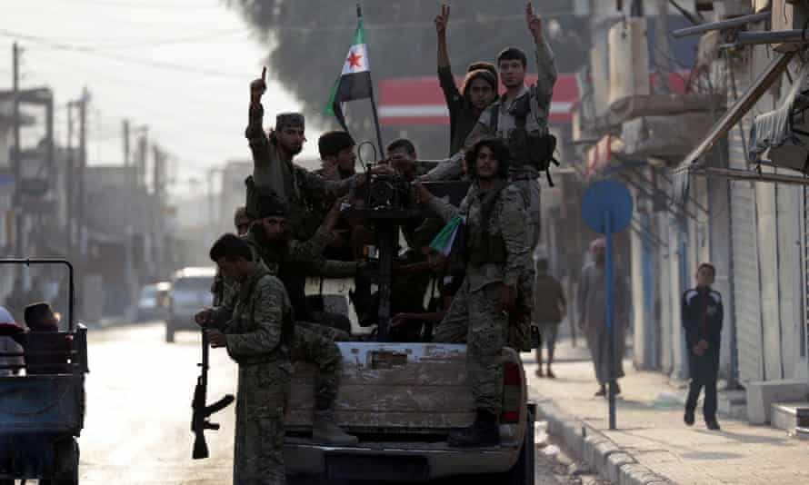 """Turkey-backed Syrian rebel fighters in the border town of Tal Abyad. The US-Turkey agreement calls for a 120-hour ceasefire in a """"safe zone""""."""
