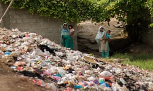 Two women holding their babies on the outskirts of Islamabad, near to a Dumpster in Mehrabadi, Islamabad