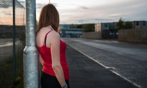 A sex worker standing against a lamppost