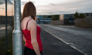 Woman dressed as a sex worker standing against a lamppost.