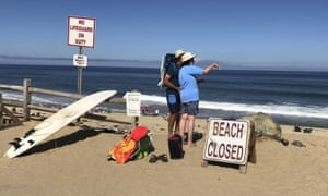 Two people look out at the shore after the shark attack at Newcomb Hollow Beach in Wellfleet, Massachusetts.