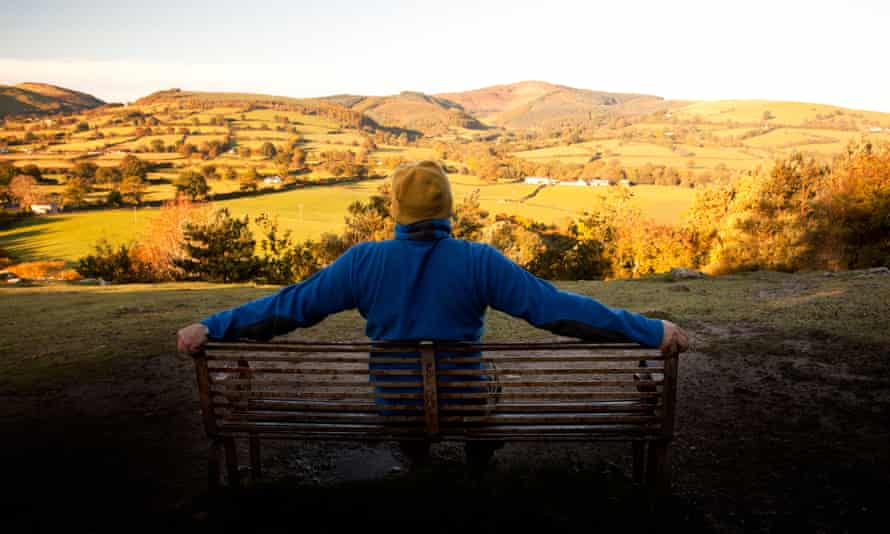 Back view of a hill walker sitting on a bench, his arms spread across the back of it, looking towards the Clwydian Range bathed in early morning light