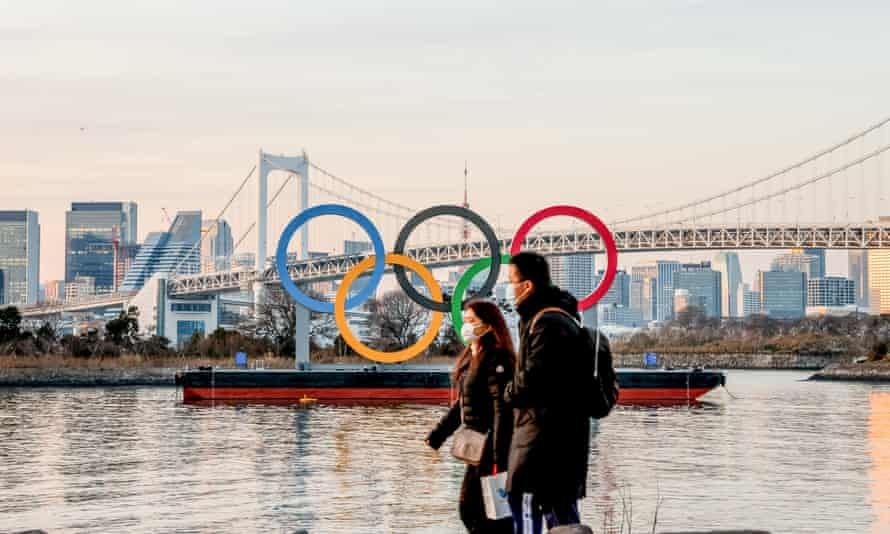 A couple wearing masks as a preventive measure against the spread of Covid-19 walks past the Olympic logo in Odaiba