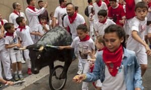 Children run in front of a toy bull during the encierro txiki (little bull running) during the fifth day of the festival
