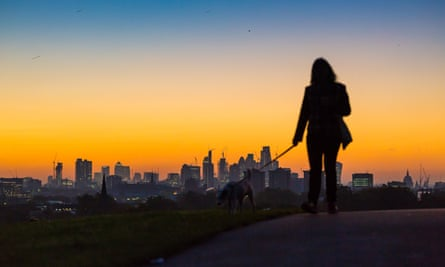 A woman watches sun rise over London's skyline.