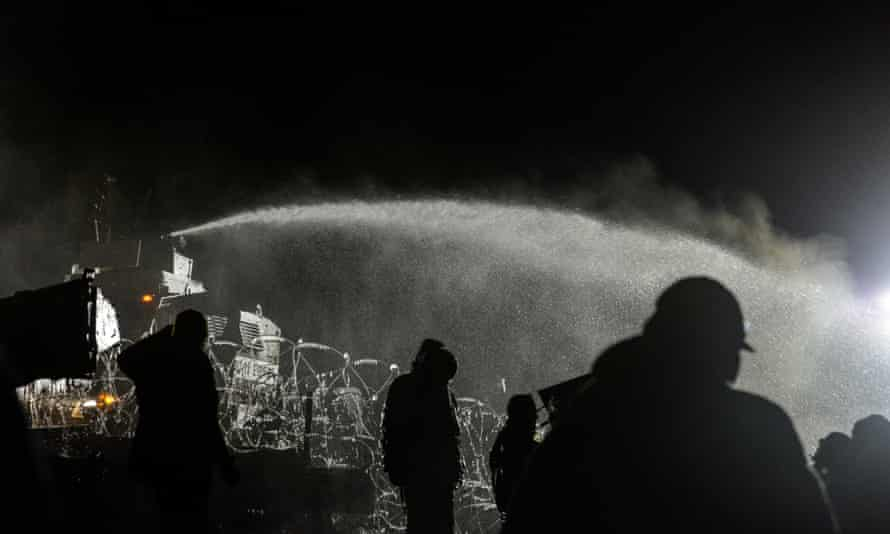Police spray water on protesters during the night of 20 November.