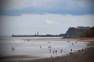 July 2020: people paddle in the sea at Sandsend beach, with the pier at Whitby in the far distance