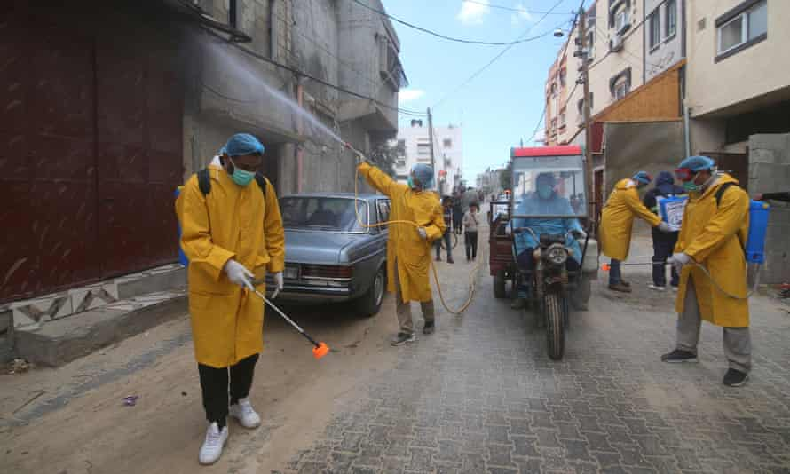 Palestinian workers in safety equipment sterilise a street