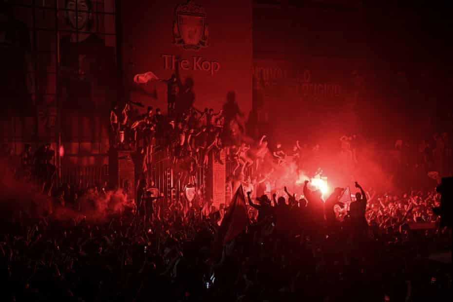 Supporters celebrate Liverpool winning the Premier League title outside Anfield stadium on 25 June following Chelsea's 2-1 victory against Manchester City.