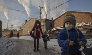 A mother and her children wear masks for protection as smoke billows from a coal-fired power plant in Shanxi, China.