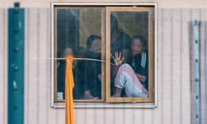 Women look out from a window in Yarl's Wood immigration removal centre in Bedfordshire