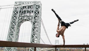 Samer Delgado shows off his strength with a one-handed handstand on the George Washington Bridge