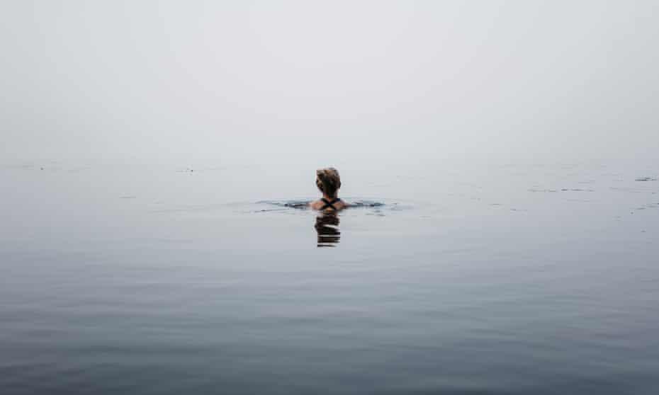 Woman swimming in sea in mist