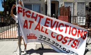 """Volunteers with the Los Angeles tenants union hang up a banner reading """"Fight evictions at all costs!"""" outside the home of a person who has received an eviction notice in East Hollywood, California."""