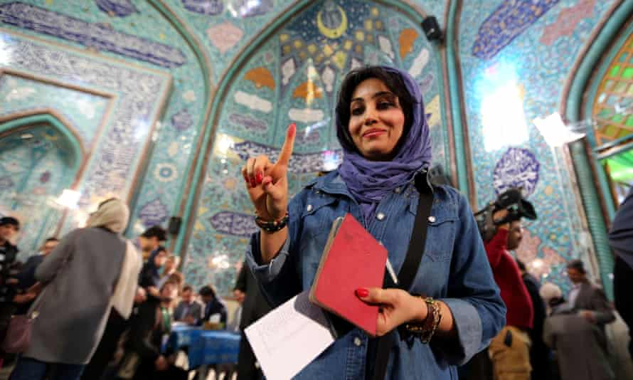 An Iranian woman shows her inked finger