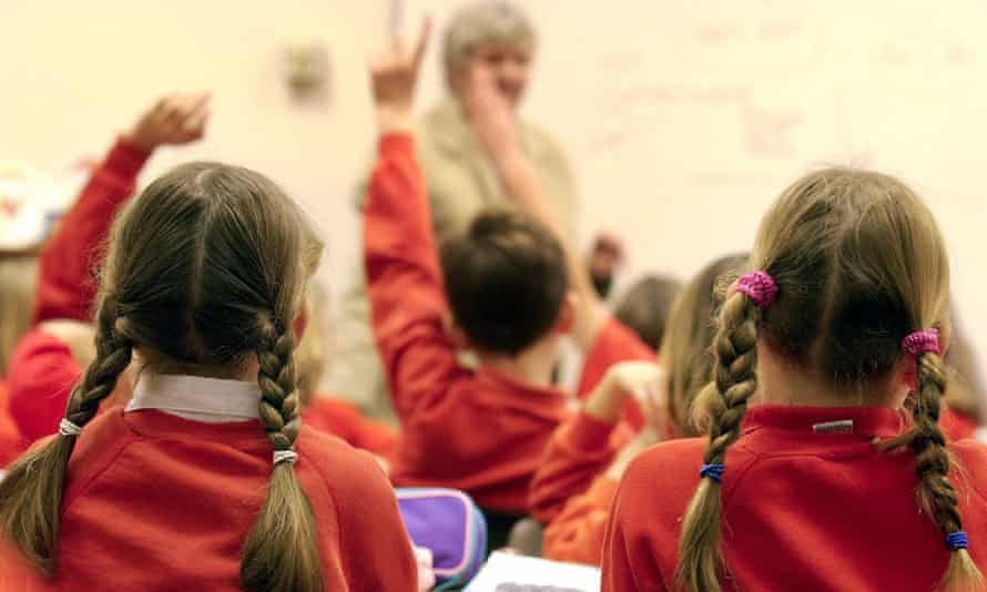 primary school students put up their hands in class