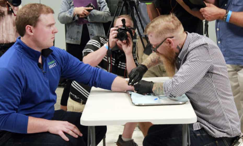 Tony Danna, vice president of Three Square Market in River Falls, receives a microchip in his left hand.