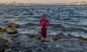 A woman stands on rocks in the sea during the religious festival of Eid al-Adha in the Sarayburnu area of Istanbul