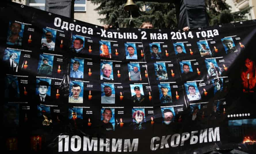 A mourner displays pictures of the dead.