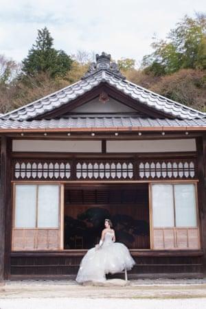 Naomi Harris in a wedding dress sitting in a pagoda in a Japanese garden