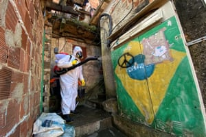 Sanitary worker cleaning in the Santa Marta favela, wearing protective equipment, Rio de Janeiro, Brazil, 13 April.