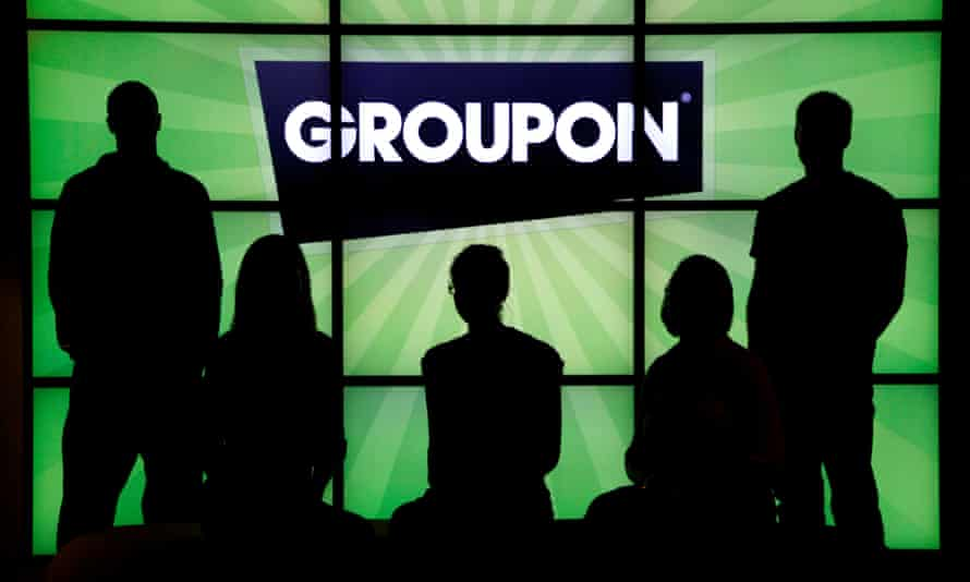 employees at Groupon pose in silhouette with the company logo