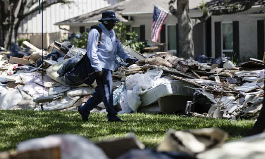 Postal worker Lonzell Rector makes his rounds among flood damaged debris from homes that lines the street in the aftermath of Hurricane Harvey in Houston.