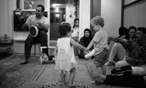Tim Buxton's son Charlie and an Iraqi child hold hands at a community centre in Soran