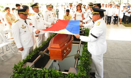 Military officers prepare to place a national flag on the coffin of the late dictator Ferdinand Marcos during the burial of Marcos at the heroes' cemetery in Manila.