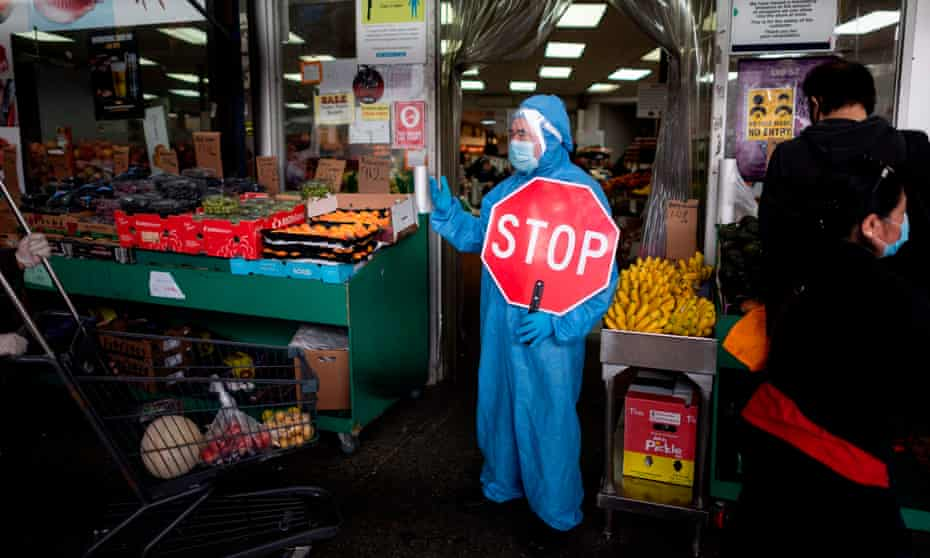 A worker wearing a full body suit holds a stop sign in front of a Food market as he manages the flow of the customers on Monday in the Jackson Heights neighbourhood of Queens in New York City.