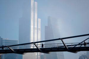 Pedestrians cross the near-deserted Millenium bridge in London