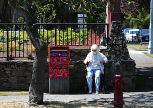 A woman sits to take a rest as heat wave hits Western Canada in Victoria, British Columbia