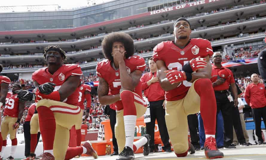 Kaepernick, centre, and San Francisco 49ers teammates protesting in 2016