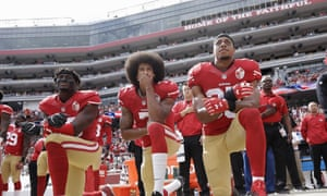 Colin Kaepernick (centre) and San Francisco 49ers team-mates 'take the knee' during the national anthem before a game on 2 October 2016