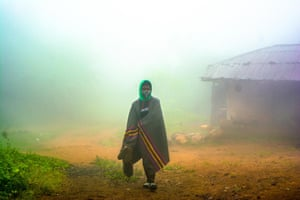 Bolatito emerges through the morning mist at Obake village on the mountain of Erin in Osun state, Nigeria, 2020