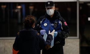 A police officer hands out masks at Atocha station, Madrid