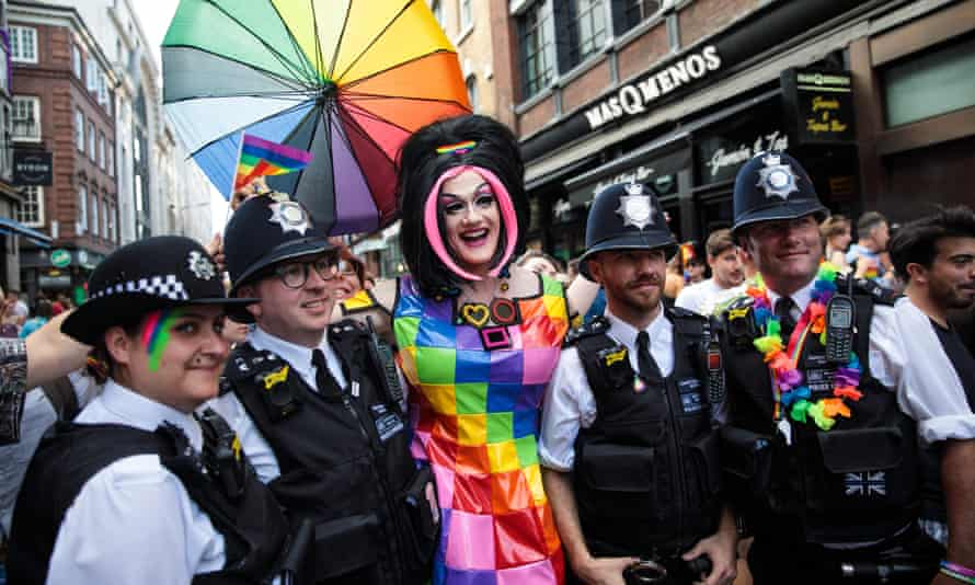 Police officers pose for a photograph with a reveller during the London Pride parade in 2017