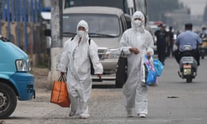 Two women wear protective suits on a street near Beijing's closed Xinfadi market