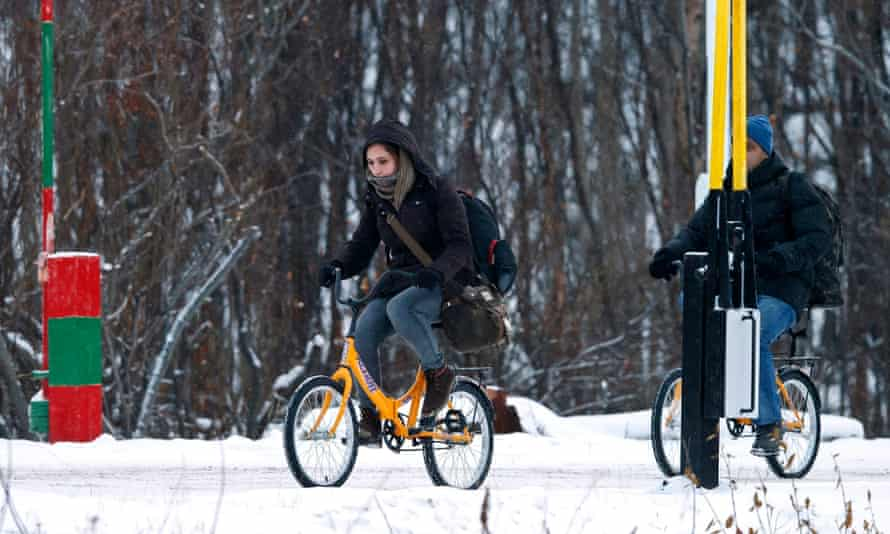 Two refugees cross the border between Norway and Russia on bicycles.