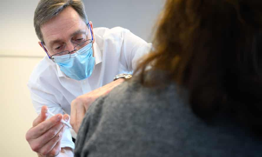 Prof Martin Marshall, the chairman of the Royal College of General Practitioners, administers a Pfizer/BioNTech vaccine in Stratford.