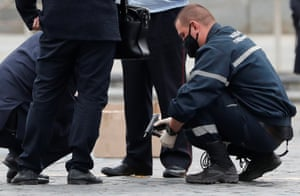 An investigator holds a gun in Red Square after opposition activist Pavel Krisevich reportedly simulated shooting himself in the head in a political protest