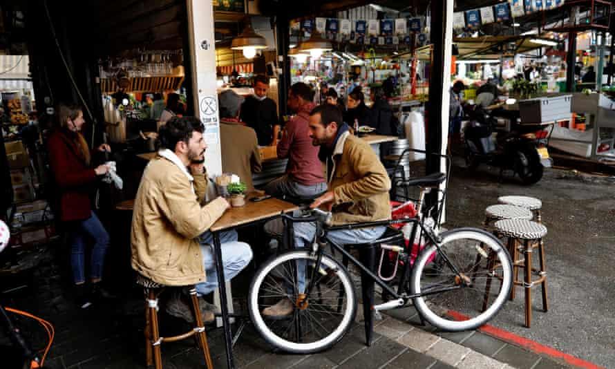 Israelis sit at a restaurant in Tel Aviv last month