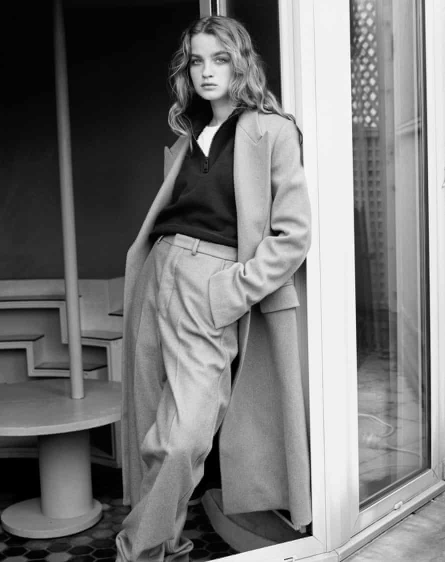 Black and white pic of a model in pale tailored trousers and long coat and a black shirt with a white t-shirt underneath
