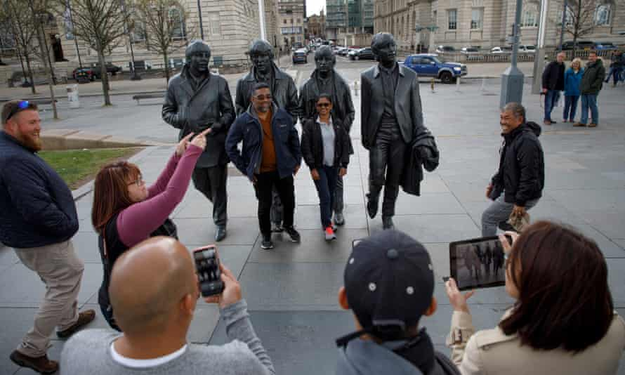 Tourists pose for pictures next to the statue of The Beatles in the Waterfront area.