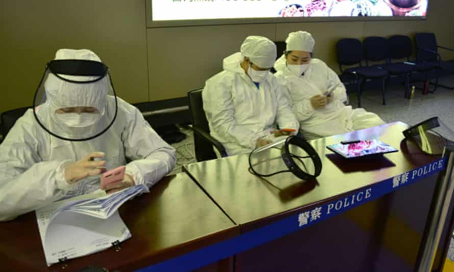 Workers in protective suits at an airport in Harbin, capital of Heilongjiang province bordering Russia, where coronavirus quarantine restrictions are in place