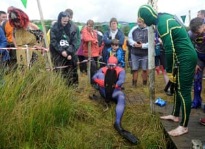 A man dressed as spiderman adjusts his flippers on the edge of the bog pond