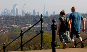 A couple take in the view of London walking in Alexandra Park.