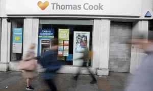 People walk past a closed Thomas Cook travel shop.