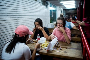 Effy, Maria Laura and Elena eat fried chicken during carnival in a corner of the city. Zillennials have an uncomplicated style. Comfort and practicality are important for them